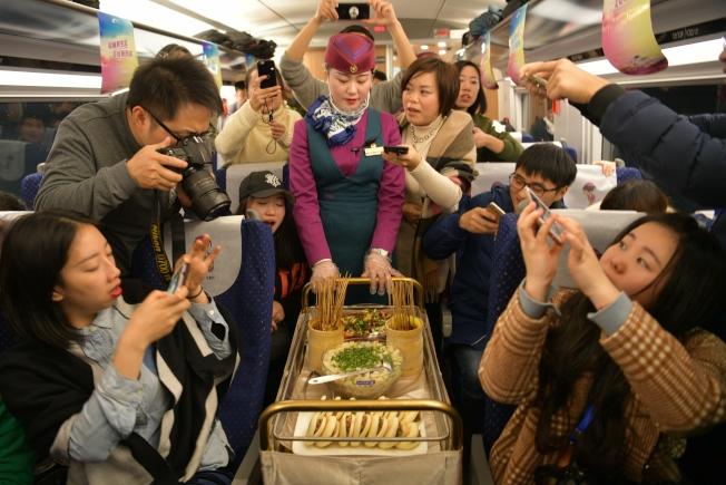 西成高鐵列車上列車員展示成都和西安的美食。 (中新社)
