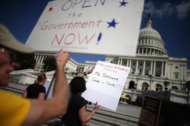 2013年聯邦政府關門,民眾在國會前舉牌要求結束僵局。(Getty Images)