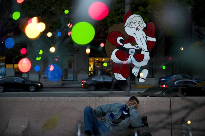 圖為47歲的遊民哈里森4日在洛杉磯市中心潘興廣場上的一條長凳上打盹。(美聯社)