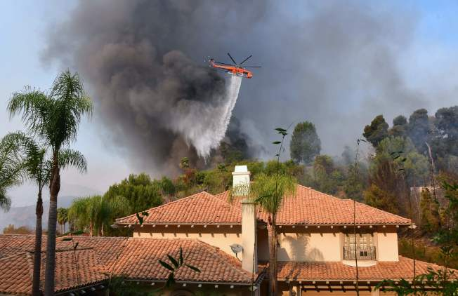 消防直升機在貝萊爾民房上空灑水滅火。(Getty Images)