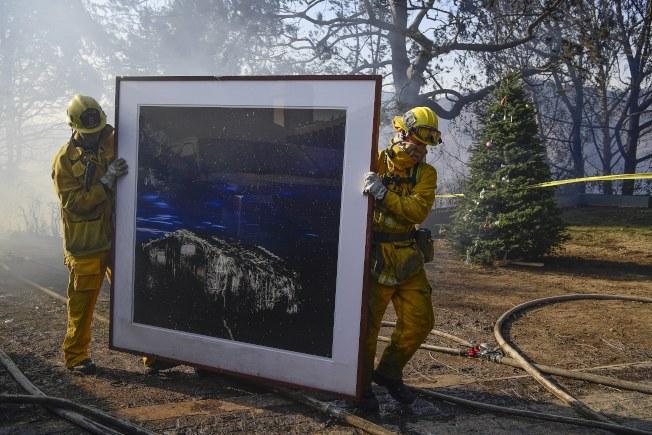 消防隊員從火場搶救出一幅畫。(歐新社)