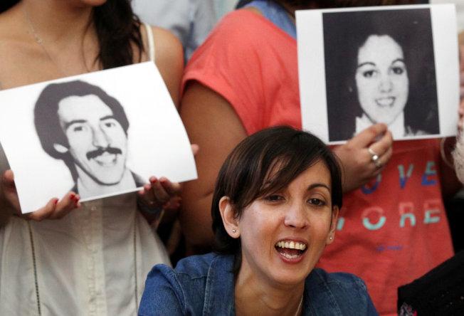 阿德里婭娜背後,活動人士手持她親生父母的照片,他們在1977年失蹤。(路透)