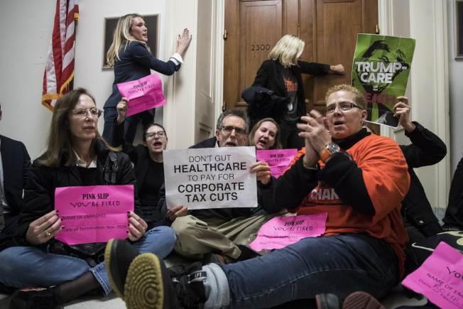 不滿稅改案的民眾到眾院共和黨議員辦公室外面舉牌抗議。(Getty Images)
