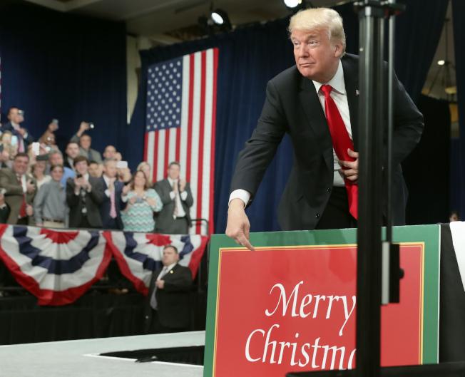 川普上月底在密蘇里州發表關於稅改演說前,手指著一塊寫有「聖誕快樂」的標誌牌。(美聯社)