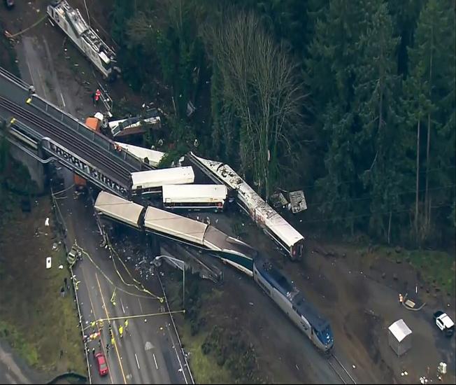 出軌的美鐵列車車廂除了散落在州際5號公路外,還有部分車廂擠壓在架高的鐵軌上。(美聯社)