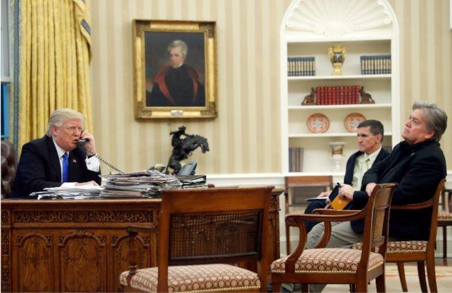 川普在白宮橢圓型辦公室與澳洲總理騰博爾通電話,前面坐著前策略長巴農(右)與前國安顧問佛林。(美聯社)