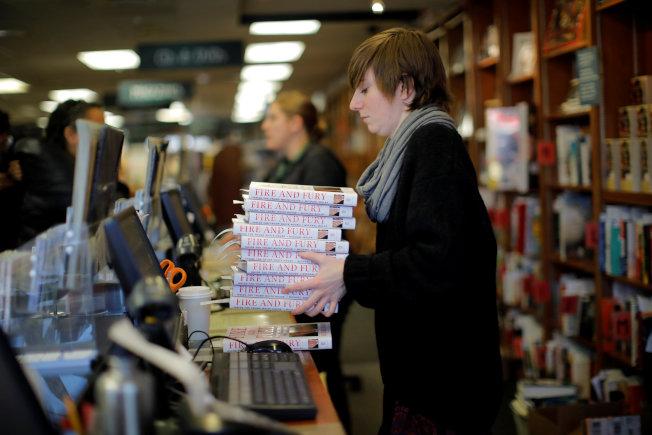 華府一家書店的店員捧著大疊「烈焰與怒火」新書。(路透)