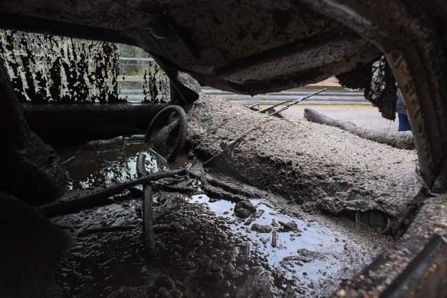 南加州柏班克發生泥石流傾洩,一輛汽車有大半埋入泥裡。(Getty Images)