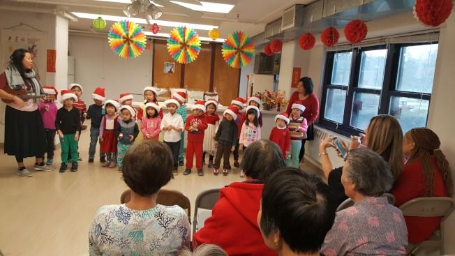 芝加哥市華德小學校長安德森日前帶領學校托兒所、一年級,學生,以及學校合唱團成員,還有學生會代表一行120人,到華埠長壽老人公寓與耆老同歡。(圖/華德小學提供)