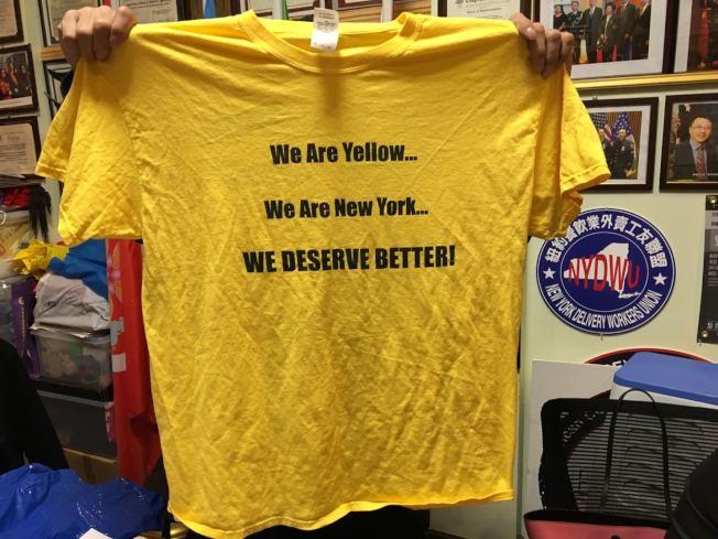 李先生手举象征出租车的黄色T恤,呼吁更多人加入25日抗议队伍。 (记者黄伊奕/摄影)
