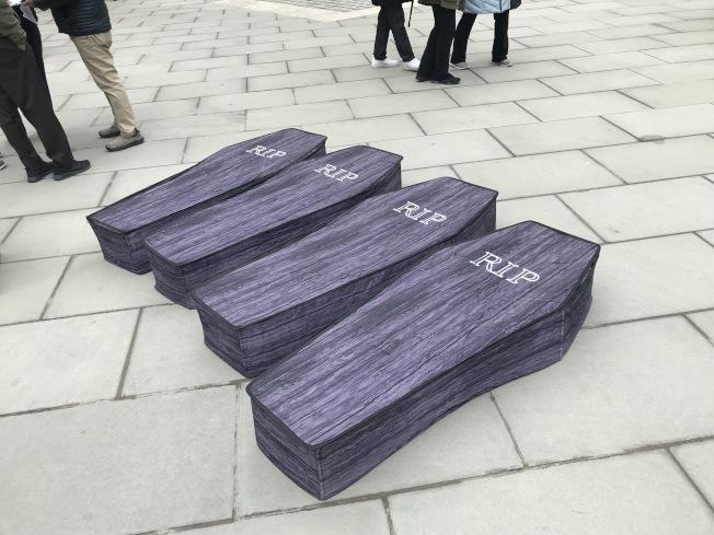 集会者在现场抬出四口仿制棺材,以悼念四位自杀的计程车司机。 (记者和钊宇/摄影)