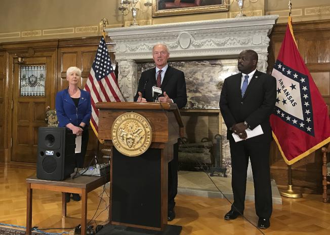 阿肯色州长哈钦森(中)12日说明该州要求享有Medicaid福利者工作的规定。 (美联社)