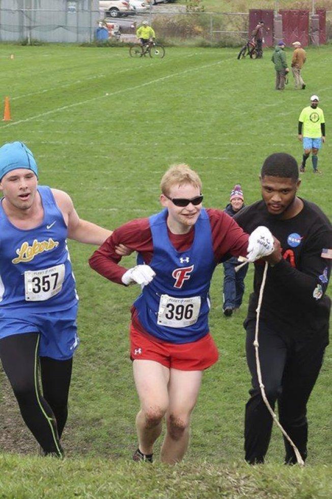 托宾(左)和陪跑员(右)一同协助视障的福特纳(中)克服斜坡。美联社