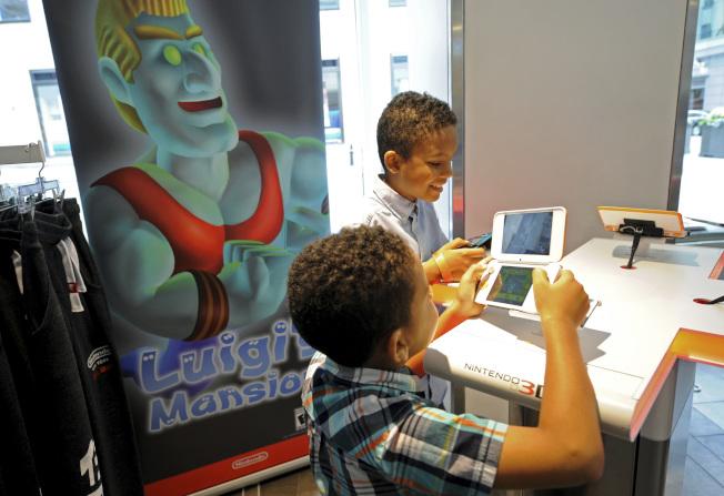 游戏主机加配件和游戏的套装组合,在黑色星期五通常会有特别优惠。图为一对兄弟在玩任天堂 2DS XL游戏机。 (美联社)