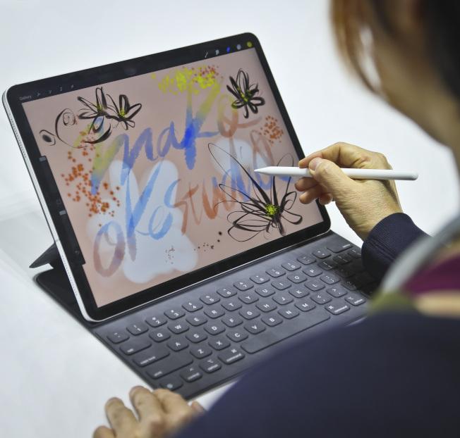 感恩节值得买苹果产品。图为一名艺术家利用iPad Pro作画。 (美联社)