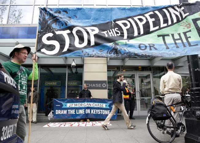 联邦法官9日封杀了从加拿大到墨西哥湾的基石XL(Keystone XL)输油管道建设计画,要求国务院重新进行环保评估。图为反对这项计画的团体在西雅图示威。 (Getty Images)