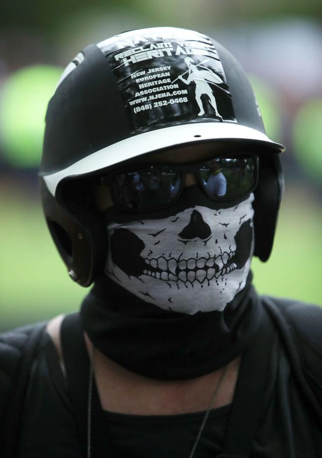 图为一名白人至上主义组织成员,头戴面罩示威。 (Getty Images)