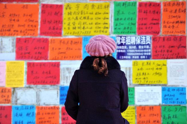 2019中国经济走势充满不确定性,图为青岛一名女性在观看西海岸新区墙上的招聘广告。 (路透)