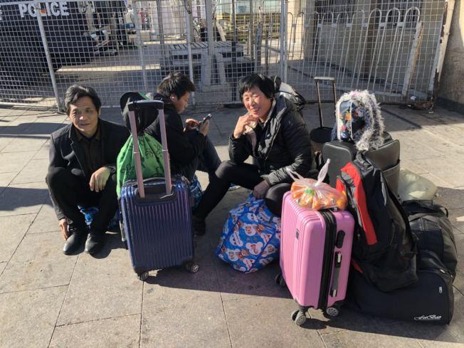 张阿姨一行人一早从天津出发到达北京站,坐在广场等待下午5点的慢车回老家山西。记者许依晨/摄影