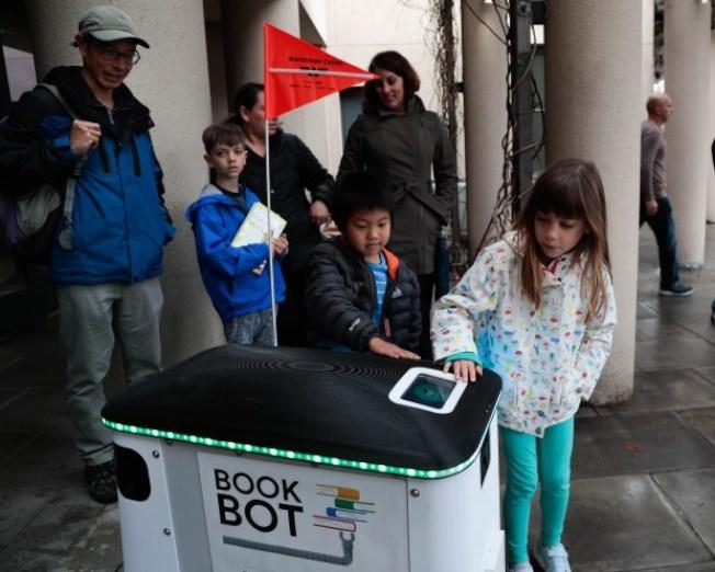 小孩看到图书机器人,反应雀跃。 (电视新闻截图)