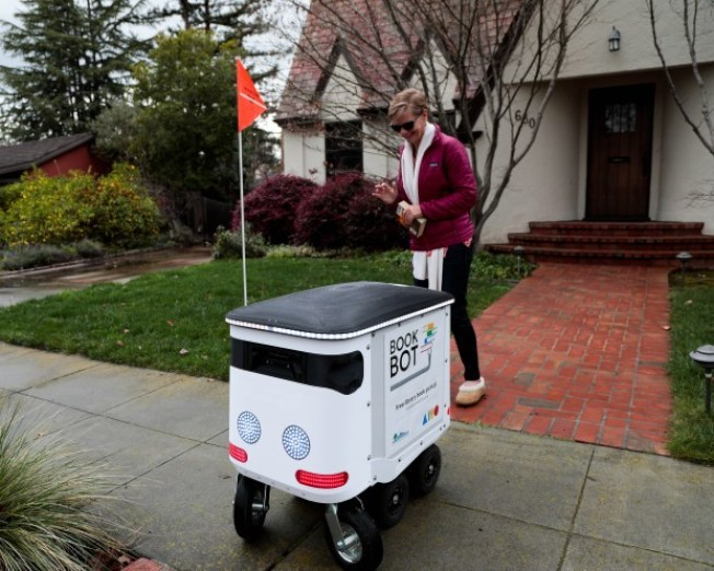 图书机器人上门,替居民将书还给图书馆。 (电视新截图)