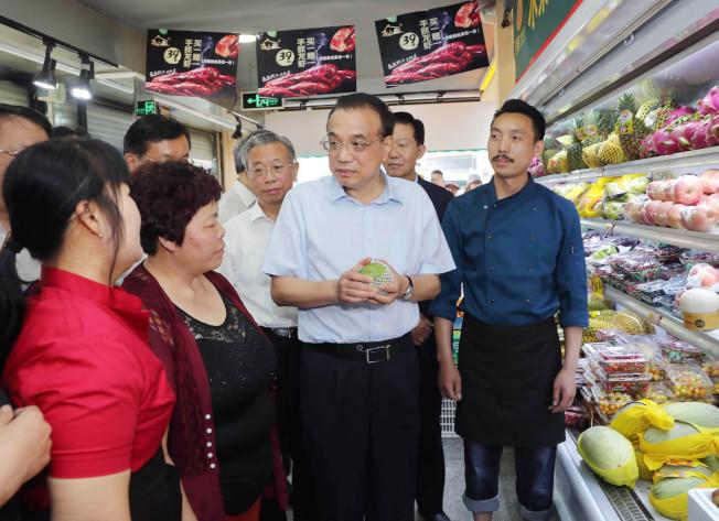 中国水果超贵,北京国务院总理李克强25日在山东潍坊、济南考察,临时停车走进一家水果店,询问水果涨价情况和原因。 (新华社)