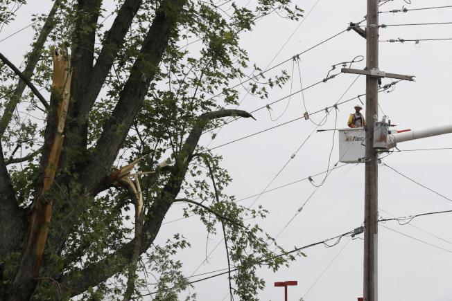 龙卷风过后,俄亥俄州成千上万居民仍然陷入缺水断电的困境,图为电力公司在俄亥州万大利亚抢修电力。 (美联社)