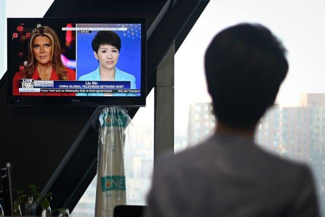 中国国营的环球电视网主持人刘欣与美国福斯商业频道主播翠西.雷根隔洋对话,中国境内并未直播。图为中国央视收到的辩论画面。 (Getty Images)