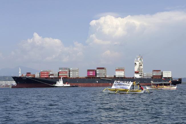 加拿大政府派来运回垃圾的货船5月30日开抵菲律宾苏比克湾时,环保人士在一旁乘着小船拉起布条,上面写着「菲律宾不是垃圾场」。 (美联社)