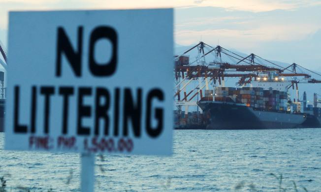 加拿大政府派来运回垃圾的货船5月30日开抵菲律宾苏比克湾时,环保人士在一旁乘着小船举起看板,上面写着「垃圾别乱丢」。美联社