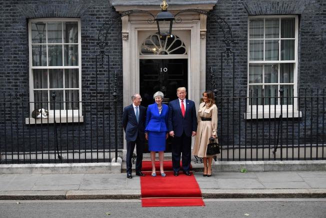 英国首相梅伊夫婿菲力浦(左至右)、梅伊、川普及美国第一夫人梅兰妮亚在唐宁街10号合影,一旁可见赖瑞窝在窗台上打盹。图╱Getty Images