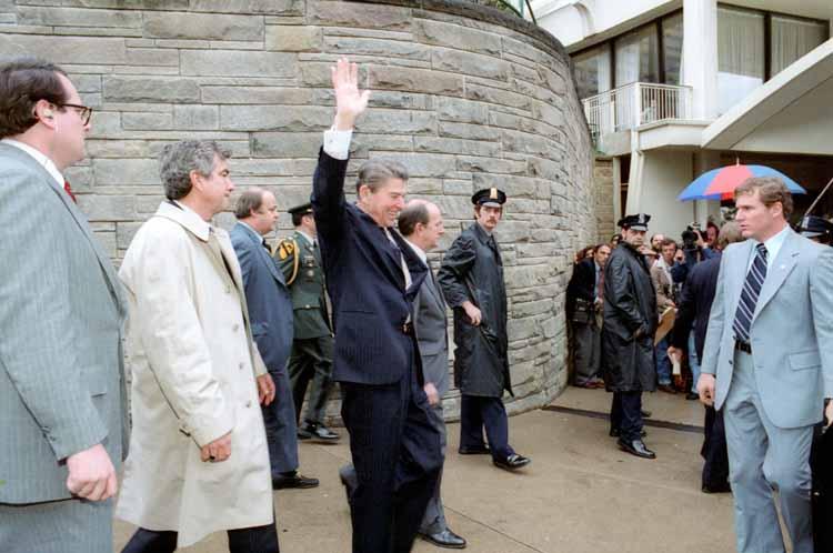 雷根步出希爾頓飯店時向等候的民眾揮手致意,特勤麥卡錫(右)在車旁等候。(Getty Images)