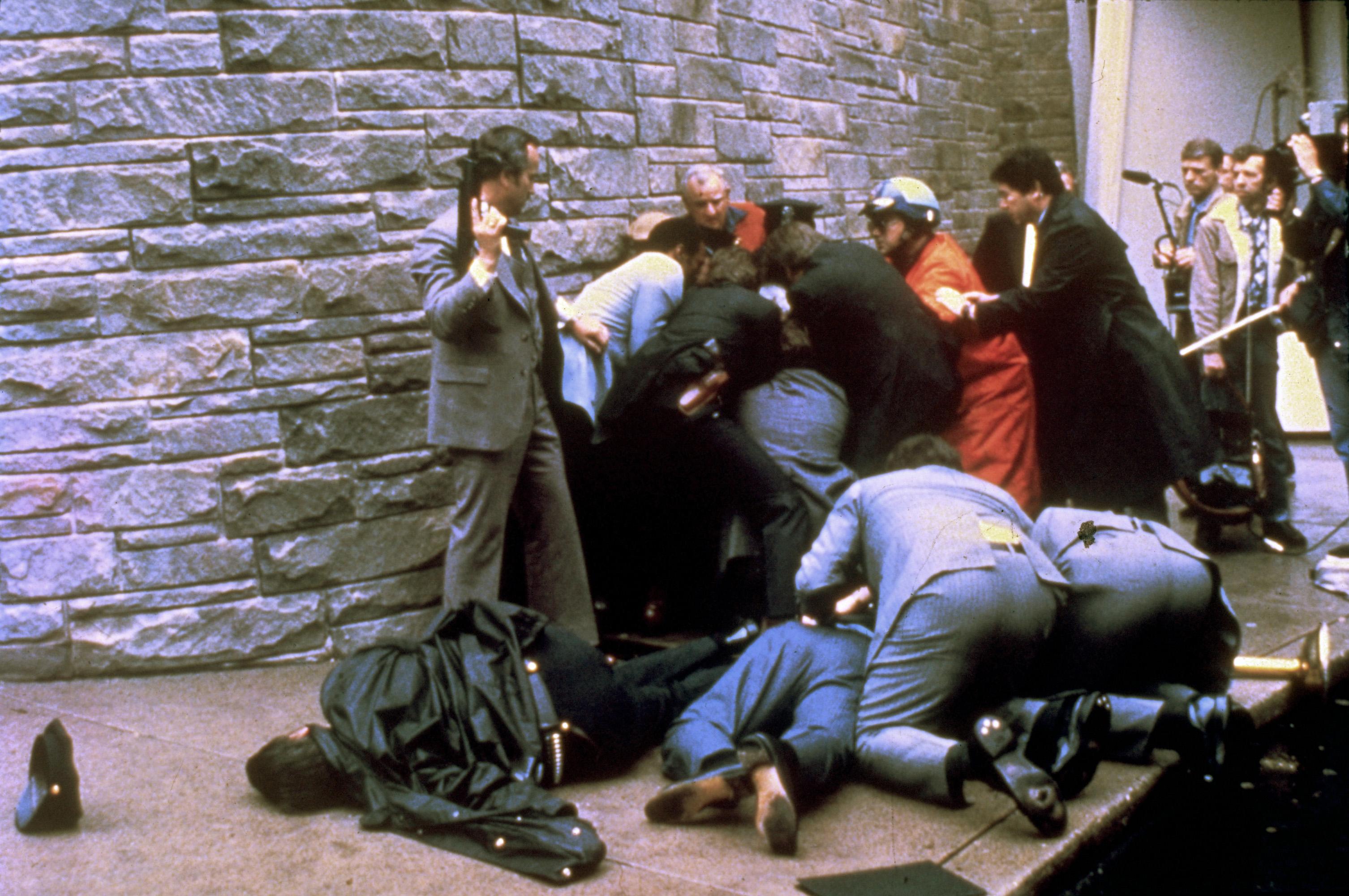 槍手被壓制在地上。Brady受傷倒在地上,特勤人員俯身檢視他的情況。左前為被擊中倒地的警官Delehanty。(美聯社)