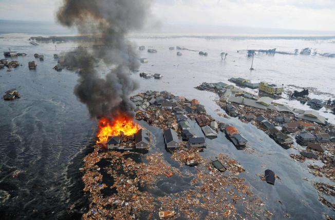 宮城縣名取市的房屋被海嘯衝垮後失火。(文:許振輝/圖:美聯社)