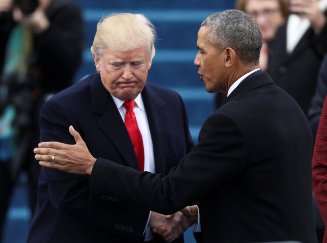 前總統歐巴馬(右)在就職大典上,拍著川普肩膀,向他打氣。(路透)