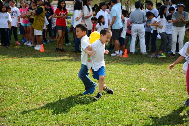 南佛州中校聯合運動會遊戲之一,小朋友們比賽背靠背夾球競走。(圖:陳肇華提供)