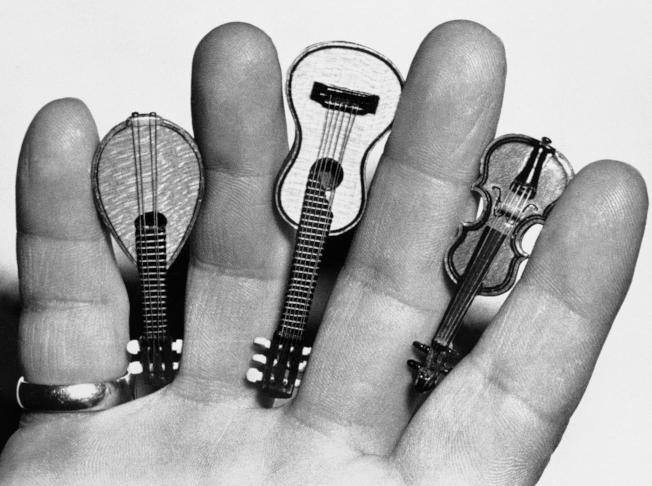 Prager Geigenbauer完成的模型樂器,其中最小的是小提琴(右)長約兩吋,與吉他、曼陀林三把琴總值約美金53萬4500元。(美聯社)