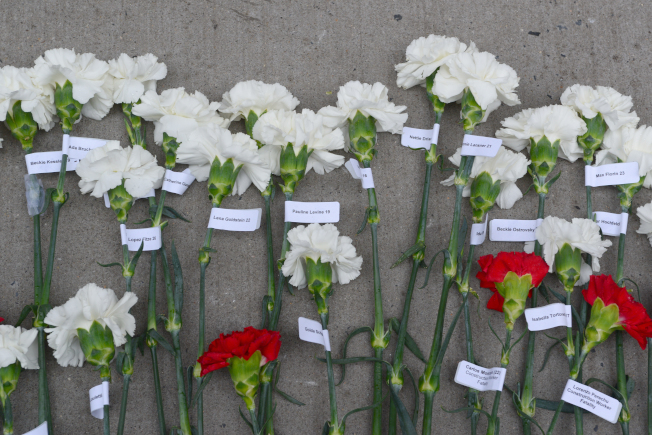 每朵花上,繫著罹難者名字及年齡。 (記者許振輝/攝影)
