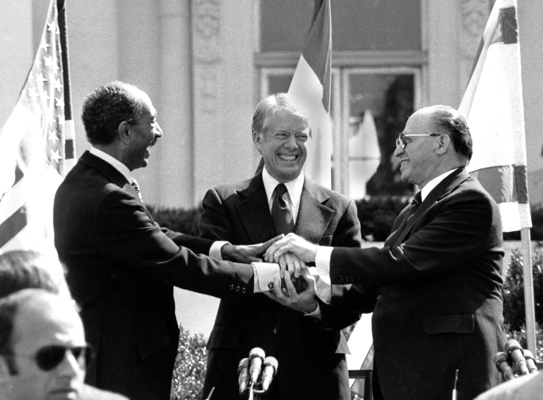 1979年3月26日,埃及總統沙達特(左)和以色列總理比金(右),在美國總統卡特的見證下,簽署「埃以和約」。(美聯社)