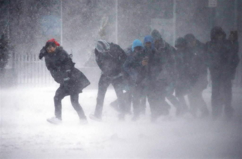 波士頓上班族頂著強勁風雪而行。(美聯社)