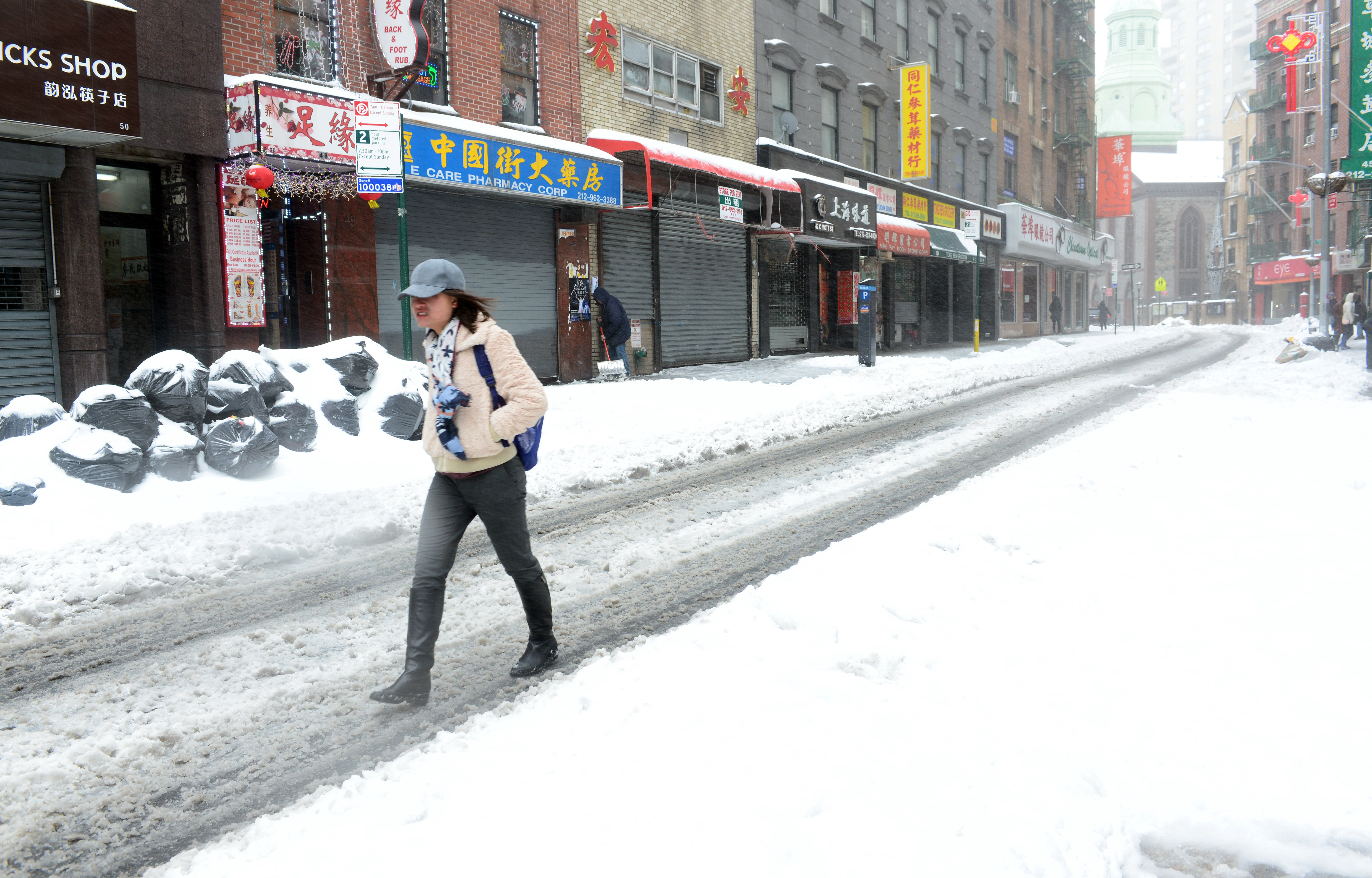 紐約市曼哈頓華埠商店幾乎全都關門,一名女遊客獨自走在空蕩蕩的勿街(Mott St.)當中。(許振輝攝影)