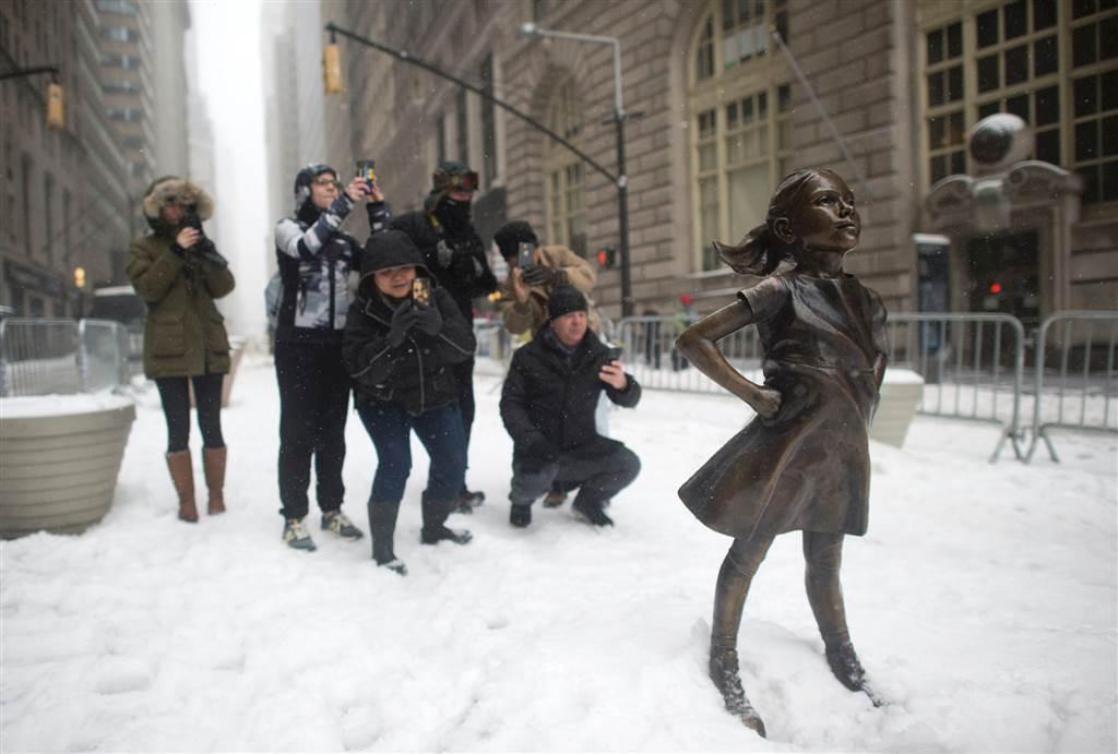 紐約市華爾街金融區於3月8日國際婦女節豎立了一座「無畏女孩」(Fearless Girl)雕像,民眾於暴風雪當天,爭相拍照。(Getty Images)