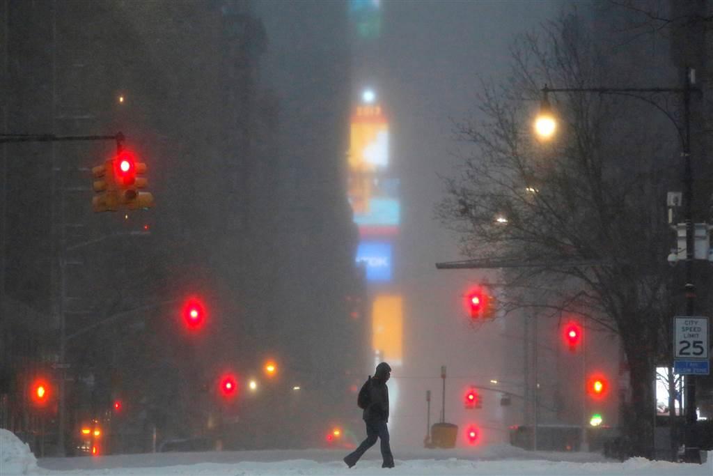 暴風雪14日侵襲美東地區,一名男子冒著風雪走過紐約市曼哈頓西59街,背後的時報廣場一片迷茫。(路透)
