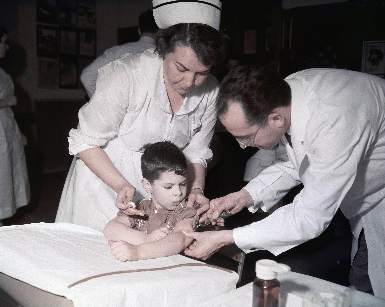 沙克博士為小孩施打沙克疫苗。(美聯社)