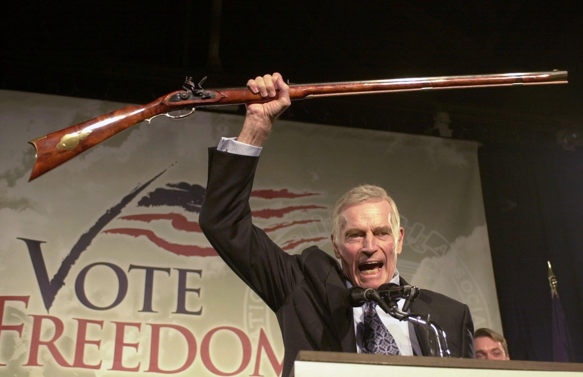 卻爾登希斯頓2002年10月21日出席全國槍枝協會會議上,高舉著步槍。(美聯社)