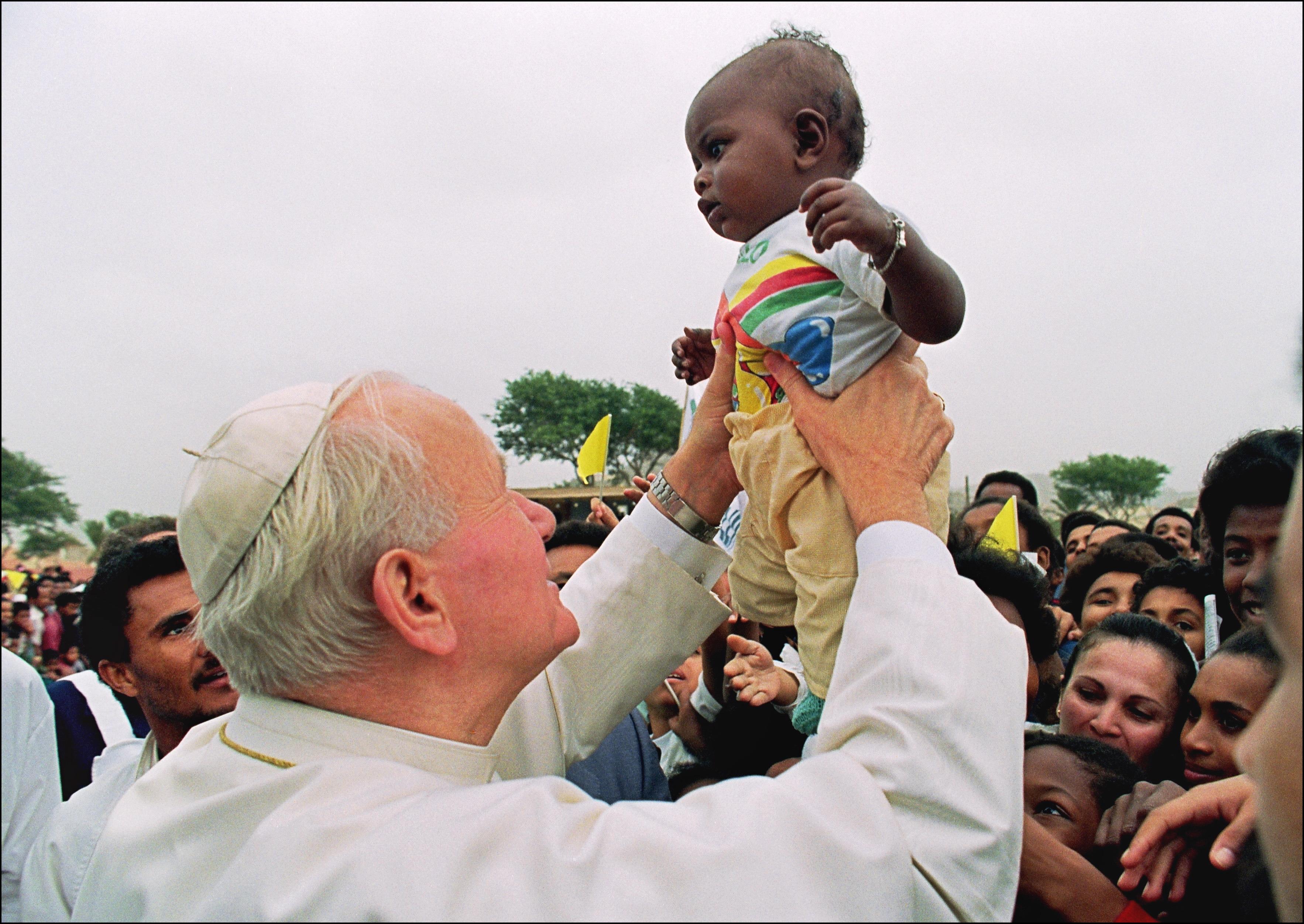 1990年1月26日,教宗若望保祿二世訪問西非的聖文森,高高舉起一名幼童。 (Getty Images)