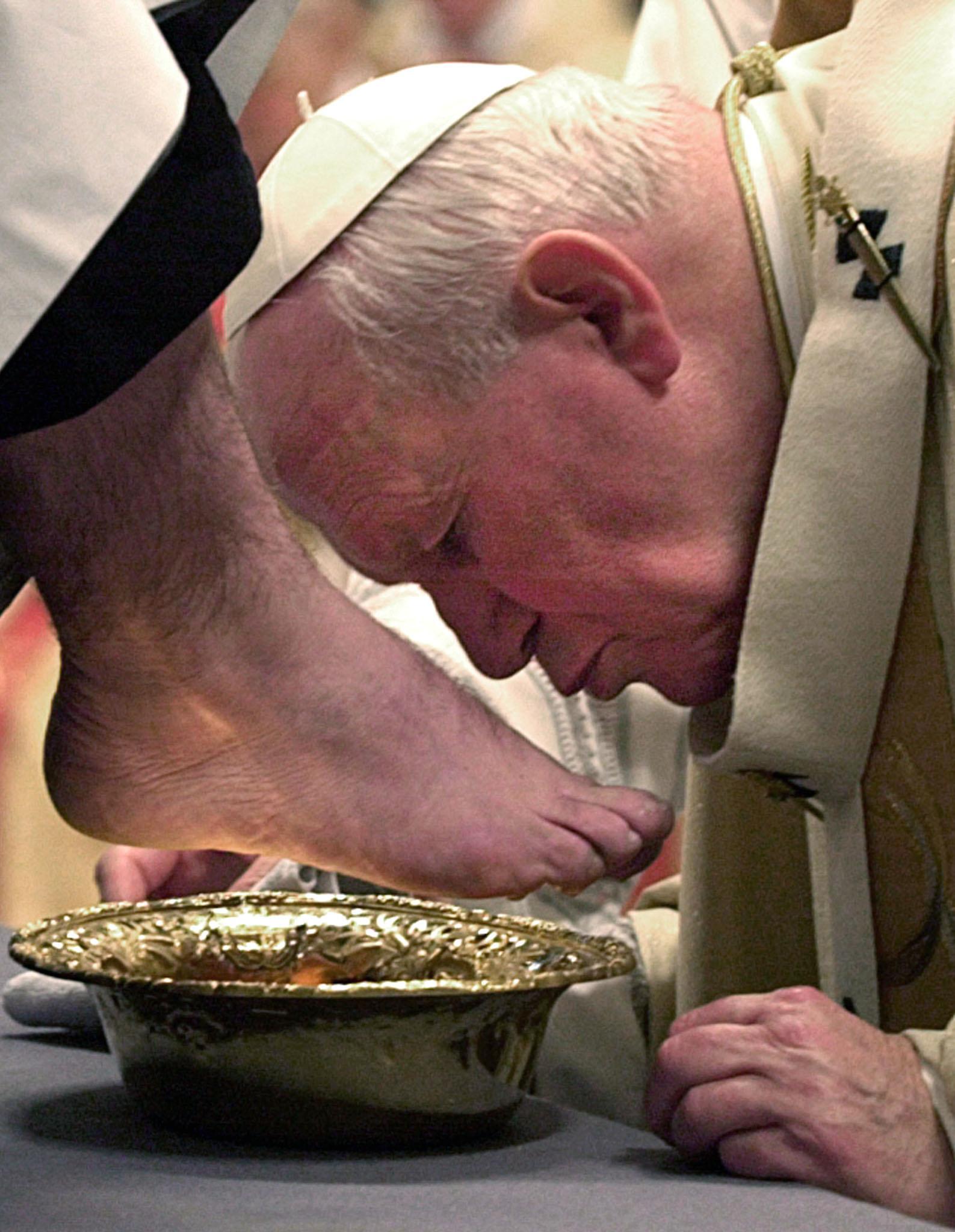 2000年4月20日,教宗若望保祿二世在彌撒中,親吻一名神職人員的腳。(Getty Images)