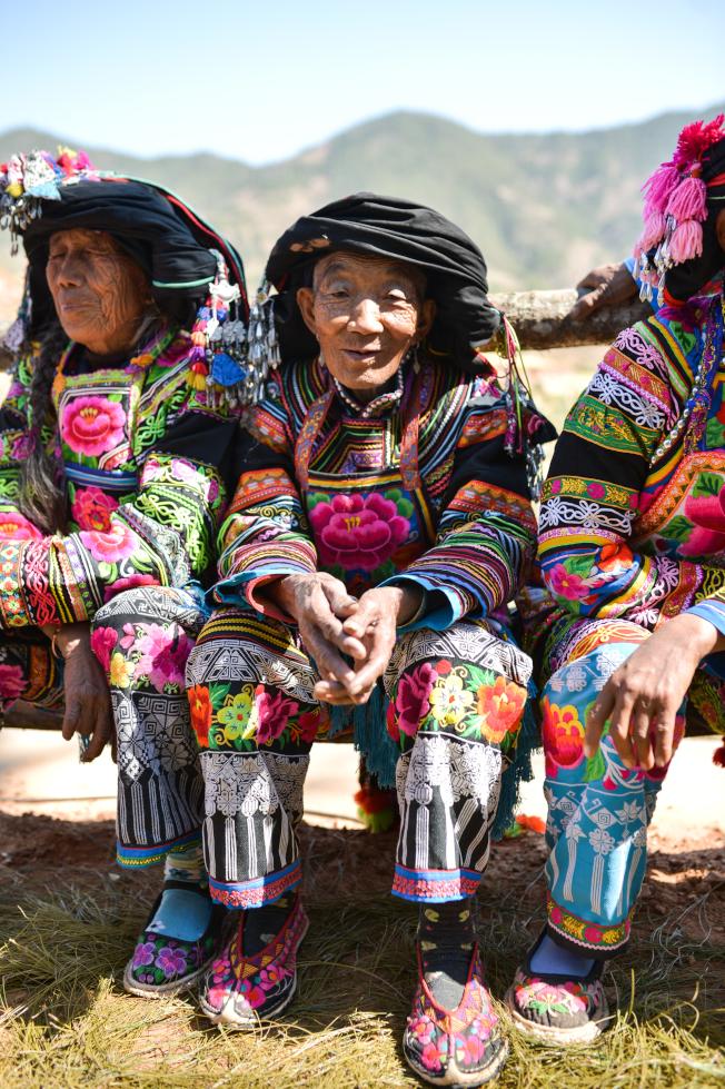 山坡上,坐滿了四鄉八寨的鄉親,他們穿著自己縫製的滿身繡花的彝裝比美、跳腳狂歡。(新華社)