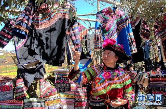 賽裝節上,李如秀在向遊客介紹自己收藏的精美繡品。(取材自新華網)
