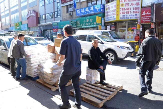 「旺角28」貨品違規占用道路,馬上被清潔局執法人員(右一)開罰。(記者朱澤人/攝影)